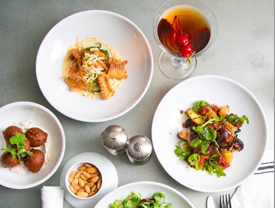 (Clockwise) Skate Bites with Napa cabbage-poblano slaw and jalapeño mayo; Manhattan; Octopus, with confit potato, dried tomato, Meyer lemon, and mustard oil; Fall Salad; smoked almonds; Lentil Fritters, with cucumber-lime yogurt. (Samira Bouaou/Epoch Times)