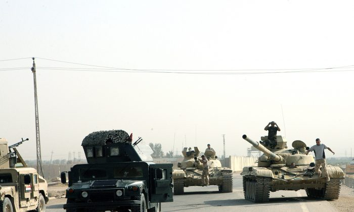 Iraqi military are seen along a main highway in Iraq's Anbar province, west of the provincial capital Ramadi, on Aug. 18, 2014, as Iraqi security forces backed by Sunni Arab tribal militia made gains against the jihadists in Iraq's Anbar province, Iraqi police said. (Azhar Shallal/AFP/Getty Images)