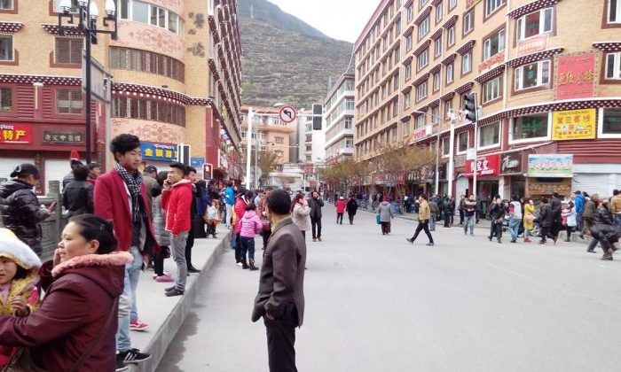 In this photo released by China's Xinhua News Agency, locals stand outside after a quake hit Kangding County in Sichuan Province, China Saturday, Nov. 22, 2014. A strong earthquake struck a lightly populated, mountainous area of western China on Saturday, killing at least one person and causing minor damage to buildings, officials and state media said. (AP Photo/Xinhua, Liu Guoqian)