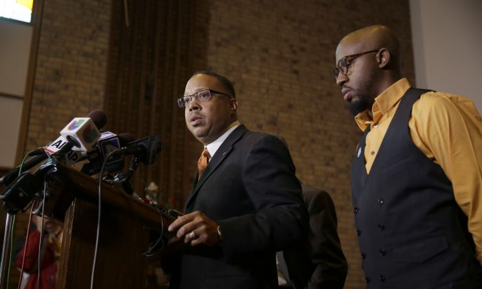 Anthony Gray, attorney for the family of Michael Brown, speaks as National Action Network Ferguson chapter president Rev. Carlton Lee (R) listens during a news conference Friday, Nov. 21, 2014, in St. Louis County, Mo. Gray and Lee spoke about preparations as citizens wait for a decision from the grand jury whether to indict Ferguson police officer Darren Wilson in the shooting of Michael Brown. (AP Photo/Jeff Roberson)