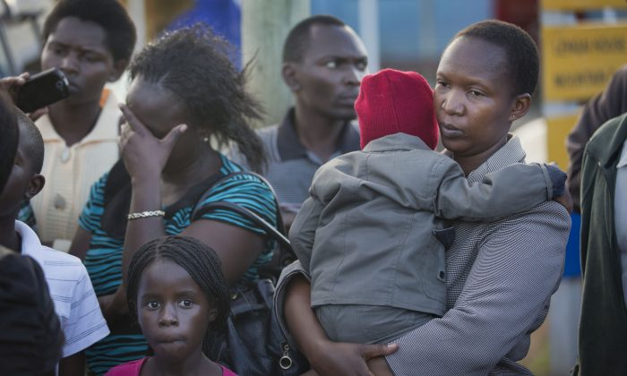 Relative Ziporah Mora (R) holds her child whom she declined to name, as she waits for news of the return of the bodies of those killed in the Mandera attack, with other relatives at Wilson Airport in Nairobi, Kenya, Saturday, Nov. 22, 2014. Somalia's Islamic extremist rebels, al-Shabab, claimed responsibility for the Saturday dawn attack on a bus in the northern Kenyan town of Mandera, near the Somali border, in which 28 non-Muslims were singled out and killed. (AP Photo/Ben Curtis)