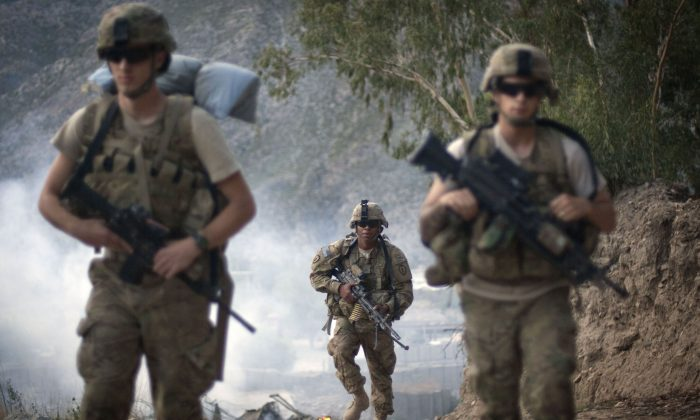 U.S. Army Pfc. Garrick Carlton, center, of Sacramento, Calif., hikes past burning rubbish to man a hilltop observation post along with fellow Pfc. Michael Tompkins, of Wadsworth, Ohio, left, and Pfc. Austin D'Amica, of San Diego, at Combat Outpost Monti in Kunar province, Afghanistan, on Sept. 10, 2011. U.S. officials say President Barack Obama has quietly approved guidelines in recent weeks to allow the Pentagon to target Taliban fighters in Afghanistan, broadening previous plans that had limited the military to counterterrorism missions against al-Qaida after 2014. (AP Photo/David Goldman)
