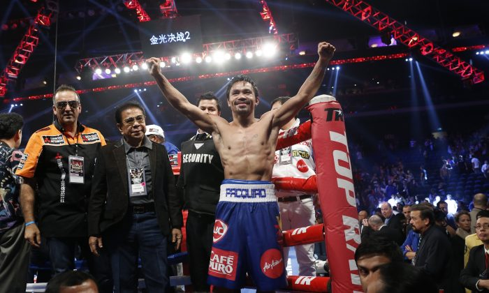 WBO welterweight champion Manny Pacquiao, center, celebrates after defeating WBO junior welterweight champion Chris Algieri of the United States during their welterweight title boxing match at the Venetian Macao in Macau, Sunday, Nov. 23, 2014. Pacquiao got the big knockdowns he desperately craved, battering Algieri around the ring Sunday on his way to a decision win in a lopsided welterweight title fight. (AP Photo/Kin Cheung)