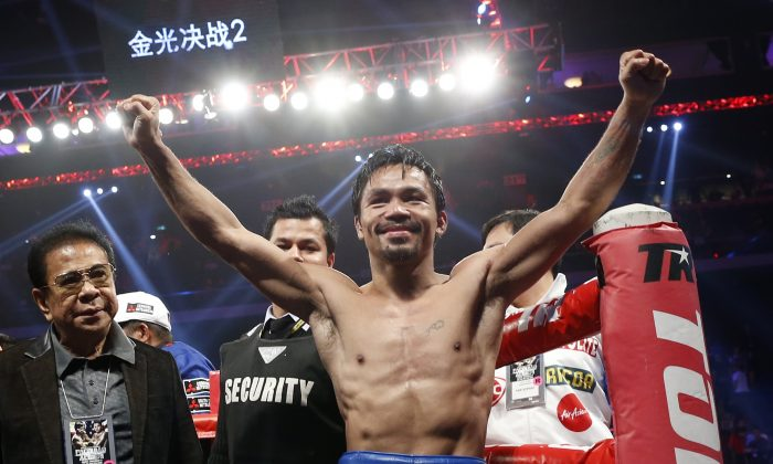 WBO welterweight champion Manny Pacquiao celebrates after defeating WBO junior welterweight champion Chris Algieri of the U.S.  during their welterweight title boxing match at the Venetian Macao in Macau, Sunday, Nov. 23, 2014. (AP Photo/Kin Cheung)