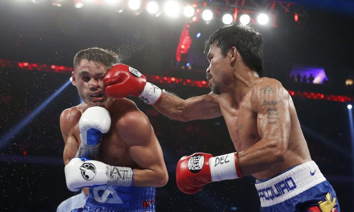 WBO welterweight champion Manny Pacquiao, right, of the Philippines lands a right on the face of WBO junior welterweight champion Chris Algieri of the United States during their welterweight boxing title fight at the Venetian Macao in Macau, Sunday, Nov. 23, 2014. (AP Photo/Kin Cheung)