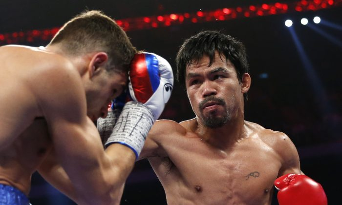 WBO welterweight champion Manny Pacquiao of the Philippines  and WBO junior welterweight champion Chris Algieri of the U.S., left, exchange punches during their world welterweight title boxing match at the Venetian Macao in Macau, Sunday, Nov. 23, 2014. (AP Photo/Kin Cheung)
