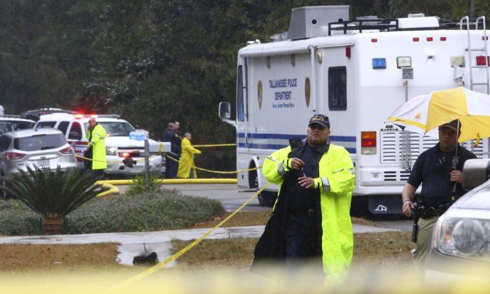 Two members of the Tallahassee Police Department on the scene of an deputy involved shooting where man set his house on fire and then fatally shot a sheriff's deputy and wounded another responding to the scene, Saturday, Nov. 22, 2014, in Tallahassee, Fla. The shooting near Florida's capital comes just two days after a police shootout at Florida State University left a gunman dead after he wounded three students. (AP Photo/Tallahassee Democrat, Joe Rondone)