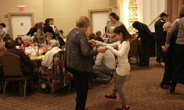 People dance at DOROT's annual Thanksgiving banquet for seniors at the Congregation Rodeph Shalom on the Upper West Side in Manhattan, N.Y., on Nov. 23, 2014. (Catherine Yang/Epoch Times)