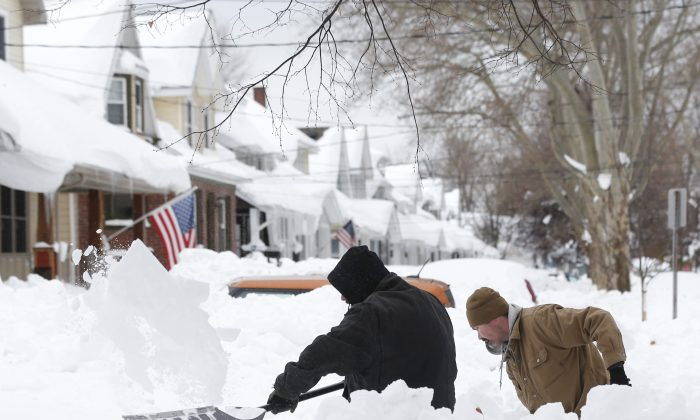 Mark Petrik and Dennis Smith dig out their south Buffalo driveway on Saturday, Nov. 22, 2014, in Buffalo, N.Y. (AP Photo/Mike Groll)