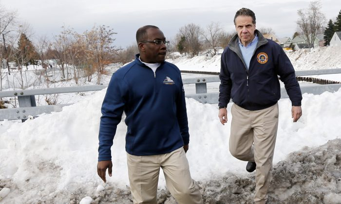 New York Gov. Andrew Cuomo, right, and Buffalo Mayor Byron Brown survey storm clean-up near Cazenovia Creek in the south Buffalo, N.Y. area on Sunday, Nov. 23, 2014. Western New York continues to dig out from the heavy snow dropped this week by lake-effect snowstorms. (AP Photo/Mike Groll)
