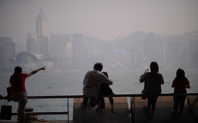 People sit in front of the city's skyline shrouded in a dense blanket of toxic smog in Hong Kong on April 15, 2013. (Philippe Lopez/AFP/Getty Images)