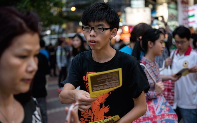 Student leader Joshua Wong (C) hands out flyers in support of the Hong Kong pro-democracy protests in the Causeway Bay area of Hong Kong on November 16, 2014. (Alex Ogle/AFP/Getty Images)