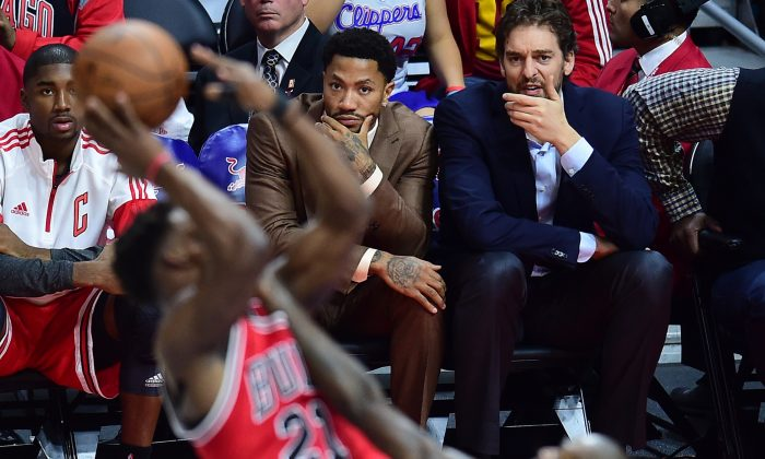 Injured players Derrick Rose and Pau Gasol of the Chicago Bulls watch from the bench in street clothes at a recent game. (AFP/Getty Images)