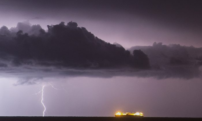 A ship sails in the Mediterranean Sea as lightning strikes, seen from the settlement of Mikhmoret, Israel, on Nov. 24, 2014. (Jack Guez/AFP/Getty Images)