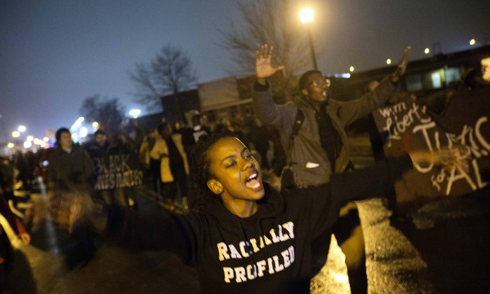 "Brittany Ferrell, of St. Louis, chants ""hands up don't shoot"" while marching through the streets protesting the August shooting of Michael Brown, Sunday, Nov. 23, 2014, in St. Louis. (AP Photo/David Goldman)"