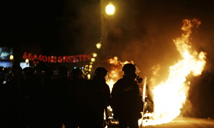 Police in riot gear move down the street past a burning police car, Monday, Nov. 24, 2014, in Ferguson, Mo. A grand jury has decided not to indict Ferguson police officer Darren Wilson in the shooting death of 18-year-old Michael Brown. (AP Photo/David Goldman)