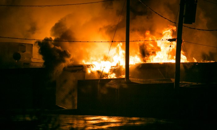 A strip mall burns after demonstrators set it on fire in Ferguson, Mo., on Nov. 24, 2014. Activists took to the streets after a grand jury decided not to indict Ferguson police officer Darren Wilson. (Benjamin Chasteen/Epoch Times)