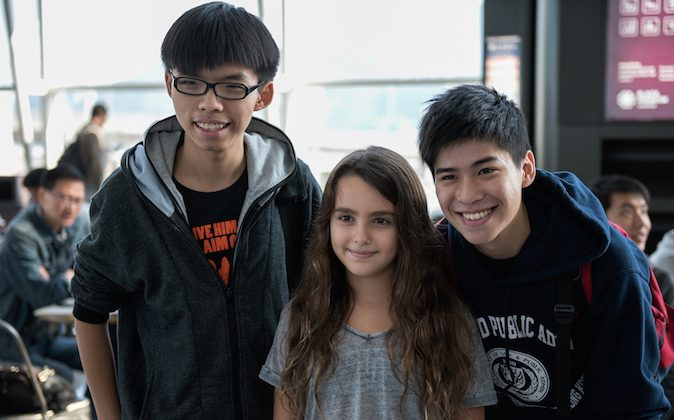 Hong Kong democracy protest leaders Joshua Wong (L) and Lester Shum (R) pose for a photo with a young girl, before fellow student leaders try to board a flight to Beijing, at Hong Kong's international airport on November 15, 2014. Three Hong Kong pro-democracy protest leaders were unable to leave the city for a planned trip to Beijing in hopes of bringing their demands for political reform to Chinese authorities. (Alex Ogle/AFP/Getty Images)