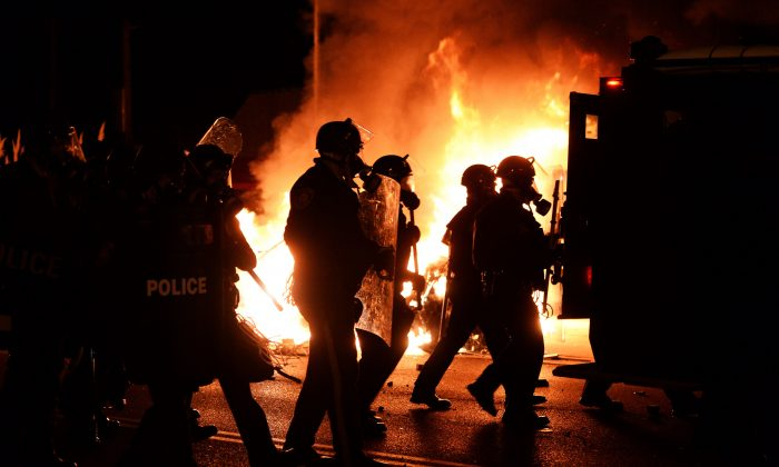 Police chase demonstrators passing a burning police vehicle during clashes between police and protesters over the decision in the shooting death 18-year-old Michael Brown in Ferguson, Missouri, on November 24, 2014. (AFP/Getty Images)
