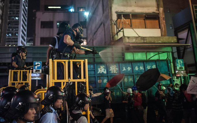 Riot police use tear spray during clash with protesters at Mongkok district on November 25, 2014 in Hong Kong. The Mongkok protest site is scheduled for clearance by baliffs this week after Hong Kong's high court authorized police to arrest protesters who obstruct bailiffs on the three interim restraining orders. (Anthony Kwan/Getty Images)