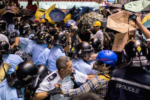 Police officers beat back pro-democracy protesters in the Mongkok district of Hong Kong on November 25, 2014. Hong Kong authorities tore down barricades at a protest site in Mongkok, the scene of some of the more violent clashes to take place during nearly two months of pro-democracy sit-ins. (Alex Ogle/AFP/Getty Images)