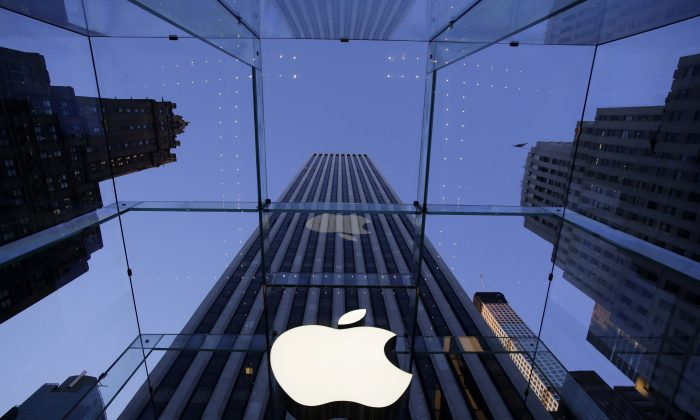 FILE - In this Sept. 5, 2014 file photo, the Apple logo hangs in the glass box entrance to the company's Fifth Avenue store, in New York. Apple, already the world's most valuable company, surpassed $700 billion in market capitalization Tuesday, Nov. 26, 2014,  as its stock hit another all-time high. (AP Photo/Mark Lennihan, File)