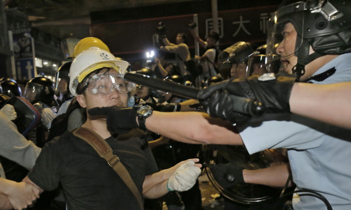 Police officers scuffle with protesters at an occupied area in Mong Kok district of Hong Kong early Wednesday, Nov. 26, 2014. An attempt by Hong Kong authorities to clear a 2-month-old pro-democracy protest camp in Mong Kok district spiraled into chaos Tuesday as hundreds more protesters flooded the crowded neighborhood, a flashpoint for earlier violent clashes with police and angry mobs. A total of 116 people were arrested, police said. (AP Photo/Vincent Yu)