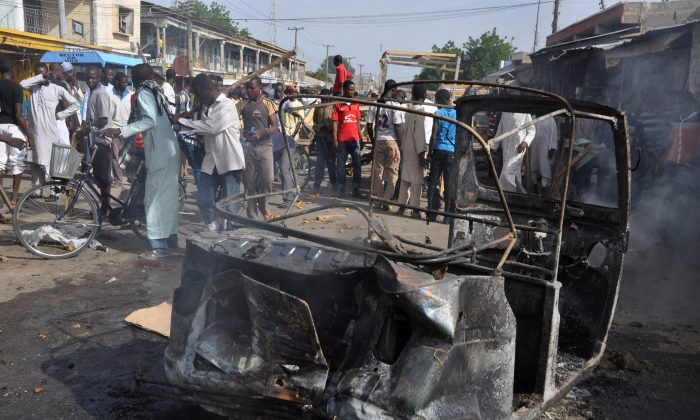 In this Tuesday, July, 2014 file photo, People gather at the scene of a car bomb explosion, at the central market, in Maiduguri, Nigeria. Today, Tuesday, Nov. 25, 2014. (AP Photo/Jossy Ola)