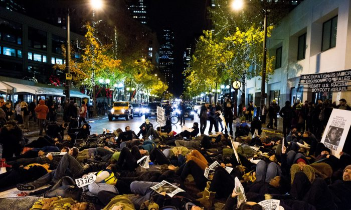 """A large group of protestors stage a """"die-in"""" on the street in response to the Ferguson grand jury decision not to indict police officer Darren Wilson in the death of Michael Brown, Monday, Nov. 24, 2014, in Seattle. (AP Photo/seattlepi.com, Jordan Stead)"""