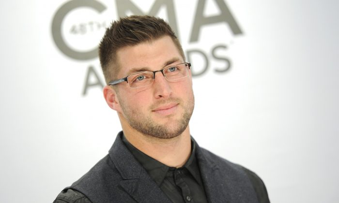 Tim Tebow arrives at the 48th annual CMA Awards at the Bridgestone Arena on Wednesday, Nov. 5, 2014, in Nashville, Tenn. (Photo by Evan Agostini/Invision/AP)