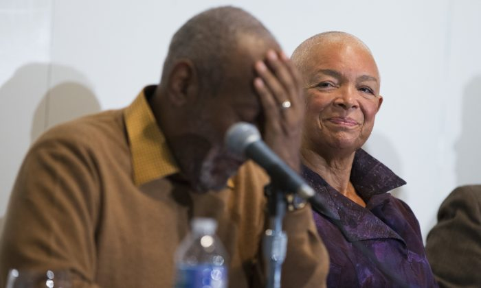 In this photo taken Nov. 6, 2014, Camille Cosby watches her husband Bill Cosby pause during a news conference about the upcoming exhibit, Conversations: African and African-American Artworks in Dialogue at the Smithsonian's National Museum of African Art in Washington. (AP Photo/Evan Vucci)