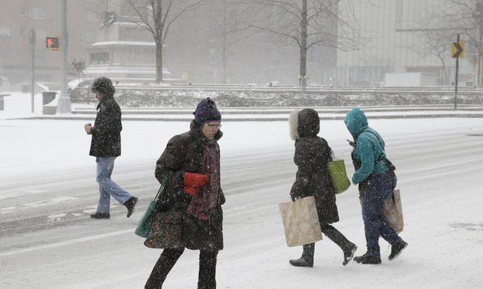 Pedestrians make their way through the snow in the Manhattan borough of New York, Tuesday, Jan. 21, 2014. (AP Photo/Seth Wenig)