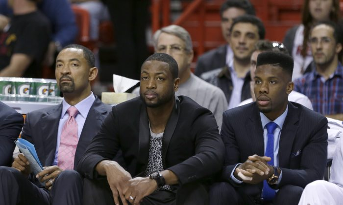 Miami Heat guard Dwyane Wade, center, and guard Norris Cole, look on from the bench with assistant coach Juwan Howard, left, during the first half of an NBA basketball game against the Charlotte Hornets, Sunday, Nov. 23, 2014 in Miami. Wade was out for his sixth straight game as he continues to work his way back from a strained left hamstring, and Cole sat out his second straight game with a dislocated finger. The Heat defeated the Hornets 94-93. (AP Photo/Wilfredo Lee)