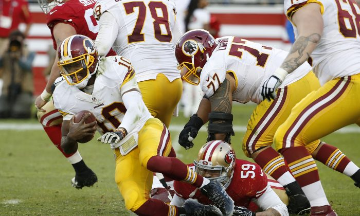 Washington Redskins quarterback Robert Griffin III (10) is tackled by San Francisco 49ers linebacker Aaron Lynch (59) during the second half of an NFL football game in Santa Clara, Calif., Sunday, Nov. 23, 2014. (AP Photo/Tony Avelar)