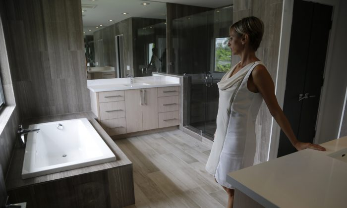 Mara Boccolini, a realtor associate with South Beach Estates, shows the master bathroom in a newly renovated waterfront property on the market during a viewing for brokers, in Miami Beach, Fla., on Sept. 24, 2014. Standard & Poor's releases its S&P/Case-Shiller index of home prices for September and the third quarter on Tuesday, Nov. 25, 2014. (AP Photo/Lynne Sladky)