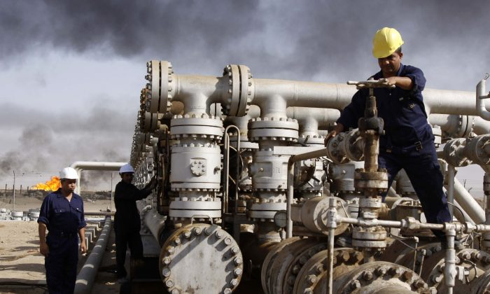 Oil personnel work at the Rumaila oil refinery, near the city of Basra, Iraq, on Dec. 13, 2009. (AP Photo/Nabil al-Jurani)