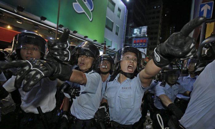 Police officers shout at protesters at an occupied area in Mong Kok district of Hong Kong on Tuesday. (AP Photo/Vincent Yu)