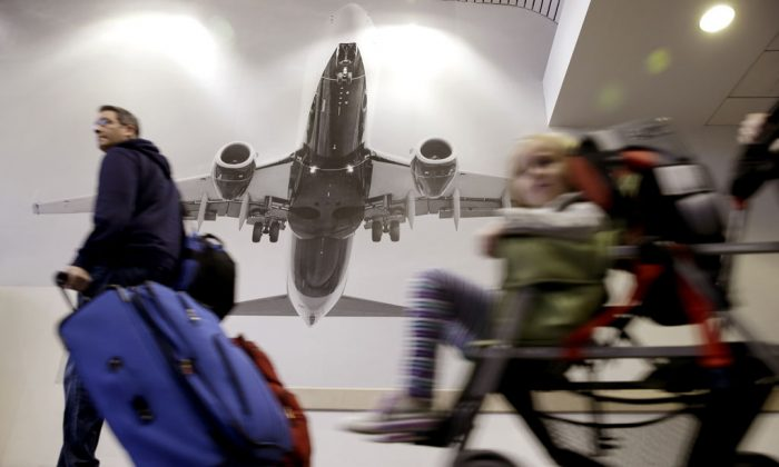 Travelers pass a large photograph of an airplane at LaGuardia Airport in New York, Tuesday, Nov. 25, 2014. A nor'easter was expected to develop along the East Coast just as millions of travelers head to their Thanksgiving destinations, bringing mostly rain close to the coast, but heavier snow further inland. (AP Photo/Seth Wenig)