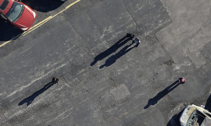 In this aerial photo, people look at a row of charred cars at a used car dealership, Tuesday, Nov. 25, 2014, in Dellwood, Mo., after they were burned in overnight protests following a grand jury's decision not to indict a white police officer in the killing of unarmed black 18-year-old Michael Brown. Monday night's protests were far more destructive than any of those that followed Brown's Aug. 9 death, with more than a dozen businesses badly damaged or destroyed. (AP Photo/Charlie Riedel)