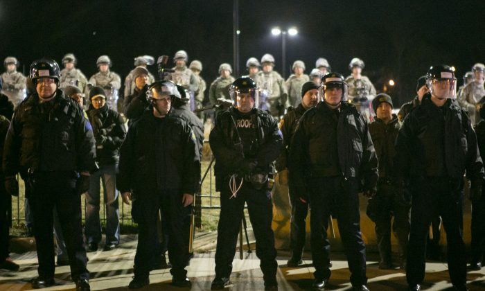 The police and the National Guard stand alert as activists across the street stage a protest in front of the Ferguson Police Station, Mo., on Nov. 25, 2014. (Benjamin Chasteen/Epoch Times)