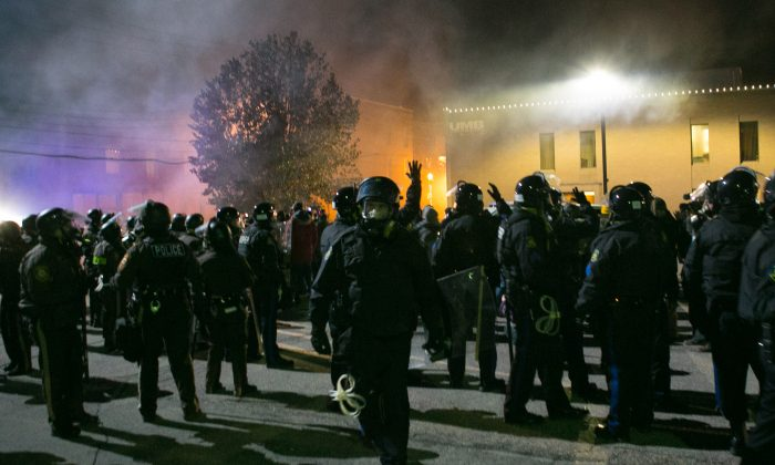Police in riot gear push everyone, including all media, back away from smoke that is arising around a building in Ferguson, Mo., on Nov. 25, 2014. (Benjamin Chasteen/Epoch Times)