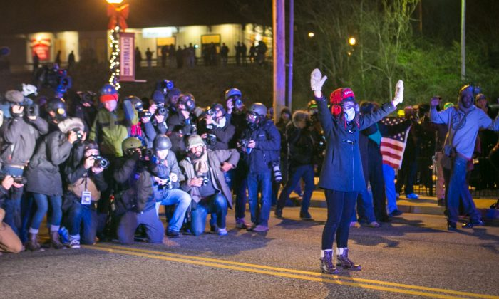 A lone woman stands with her hands up in front of the police making an announcement for her to leave the street, as media take shots of her from behind, in Ferguson, Mo., on Nov. 25, 2014. (Benjamin Chasteen/Epoch Times)