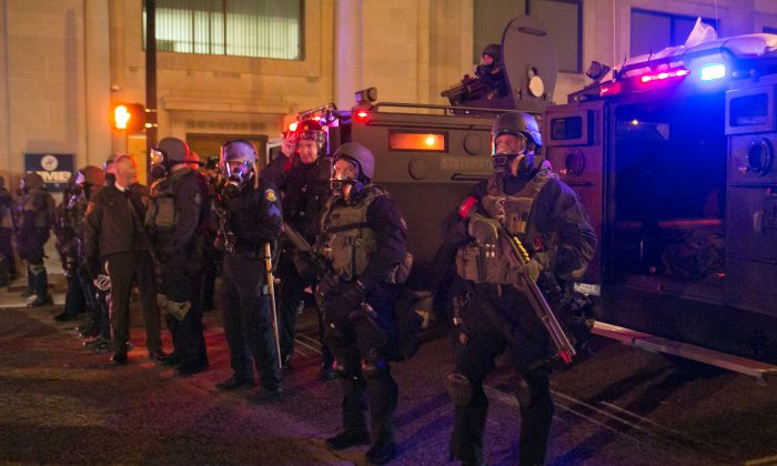 Police in full on riot gear stand by after they fired tear gas at activists not too long before in Ferguson, Mo., on Nov. 25, 2014. (Benjamin Chasteen/Epoch Times)