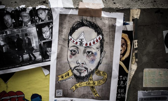 A poster depicting Civic Party member Ken Tsang, who was beaten by plainclothes police officers, is displayed at the main protest site in the Admiralty district of Hong Kong on Oct. 23, 2014. Seven officers involved in the beating were arrested on Nov. 26 following police investigation. (Philippe Lopez/AFP/Getty Images)