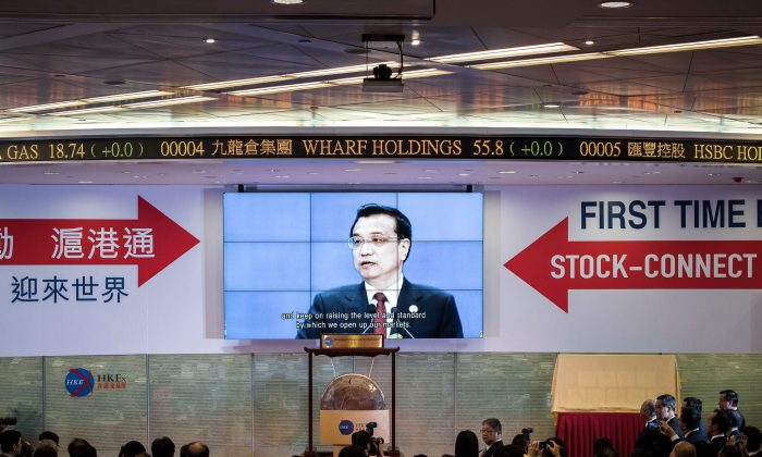 Guests watch a recorded video of China's Premier Li Keqiang (top C) during the launch of the Shanghai-Hong Kong Stock Connect in Hong Kong on Nov. 17, 2014. Officials had threatened that the opening of the new exchange would be delayed by the Umbrella Movement, which legislator Sin Chung-kai was part of an attempt to threaten Hong Kong into abandoning the movement. (Philippe Lopez/AFP/Getty Images)