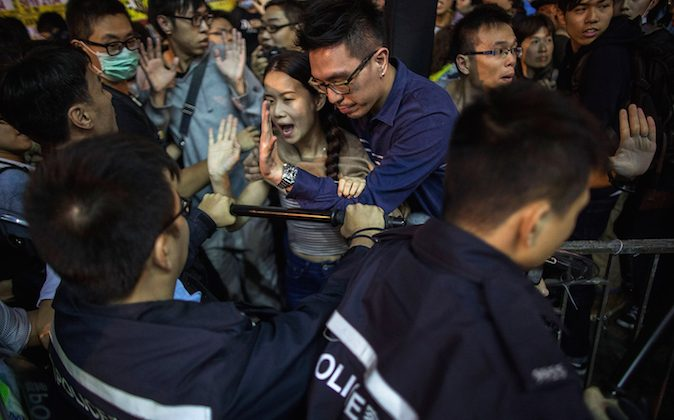 Pro-democracy protesters and pedestrians clash with police on a street in Mong Kok on November 26, 2014 in Hong Kong. (Lam Yik Fei/Getty Images)