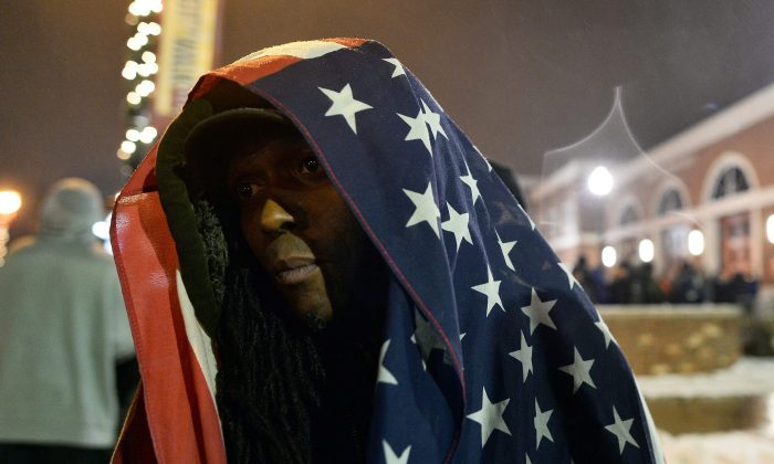A protester covers himself with a US flag during a demonstration outside the police station in Ferguson, Mo., on Nov. 26, 2014. (Jewel Samad/AFP/Getty Images)