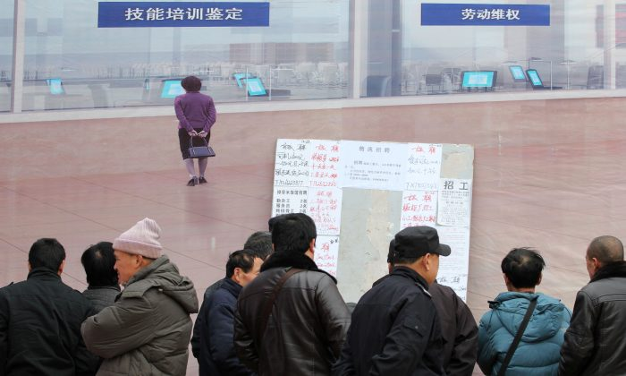 This picture taken on February 17, 2014 shows migrant workers reading a bulletin board at a job market in Qingdao, east China's Shandong province. (STR/AFP/Getty Images)