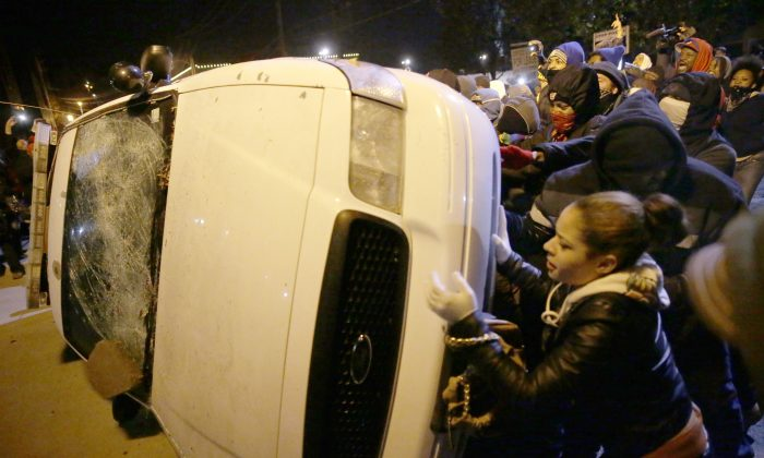 Protesters vandalize a police vehicle outside of the Ferguson city hall in Tuesday, Nov. 25, 2014, in Ferguson, Mo. Missouri's governor ordered hundreds more state militia into Ferguson on Tuesday, after a night of protests and rioting over a grand jury's decision not to indict police officer Darren Wilson in the fatal shooting of Michael Brown, a case that has inflamed racial tensions in the U.S. (AP Photo/David Goldman)