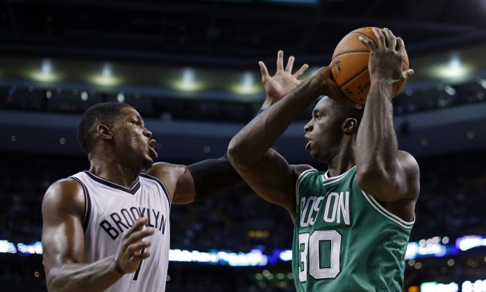 Boston Celtics forward Brandon Bass (30) prepares to shoot against Brooklyn Nets guard Joe Johnson (7) in the first quarter of an NBA basketball game in Boston, Wednesday, Oct. 29, 2014. (AP Photo/Elise Amendola)